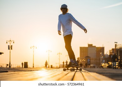 Young skaterboy riding longboard on the boardwalk, silhouette on sunset