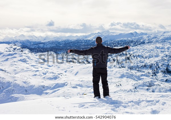 Young skier, enjoying the view from top of mountains in Austrian ski resort on a sunny winter day, happiness and freedom concept