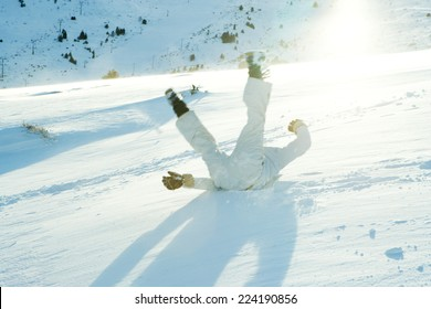 Young skier falling down ski slope, legs in the air, rear view