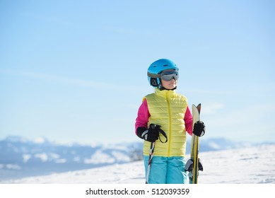 Young skier girl  in the mountains on a sunny day