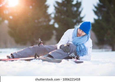 Young skier screaming and keeping his hands on hurt knee while lying in snowdrift