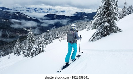 Young skier stands on a gravelly slope with her skis. The mountain slopes are covered with snow. Pine trees covered with snow. - Shutterstock ID 1826559641
