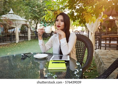 Young skilled asian female freelancer starting working day early in morning drinking coffee to wake up making new design for website with new advertising content using modern touch pad and wifi
