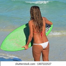 Young skim boarder holding a green skim board