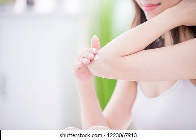 Young skin care woman applying elbow cream at home