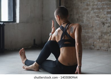 young skinhead woman doing twist stretching yoga exercise - ardha matsyendrasana indoor