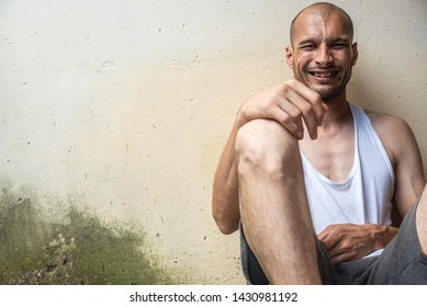 Young skinny anorexic bald positive and happy smiling homeless man sitting on the urban street in the city or town near white wall with big smile, homelessness social documentary concept
