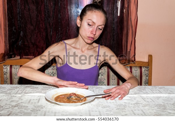 Young skinny anorexic girl or woman with anorexia nervosa disorder refusing to eat food