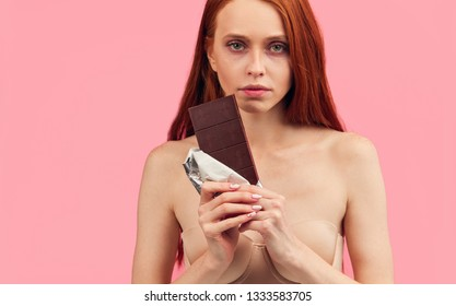 Young skinny anorexic unhealthy woman is fighting with temptation to eat chocolate bar, looking looking miserable at camera, isolated over pink background