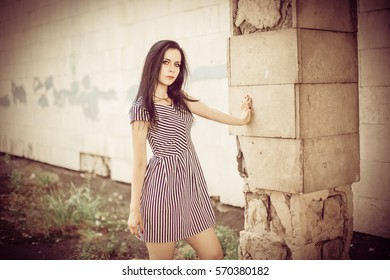 young skinny charming lady posing in short dress black and white with stripes. nice and sexy brunette demonstrating fashion pose on the background of the abandoned buildings, fashion vintage colors