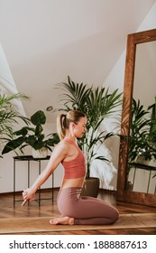 Young skinny fit yoga woman instructor in leggings and sport top is practicing stretch pose in a white yoga studio full of green houseplants. Relaxation of the nervous system. Healthy active lifestyle
