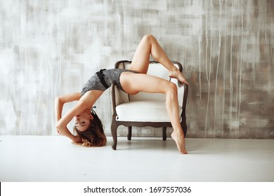 Young skinny sportive flexible woman sitting on chair in the light grey studio in her home during quarantine. What to do at home during self-isolation. Stay home
