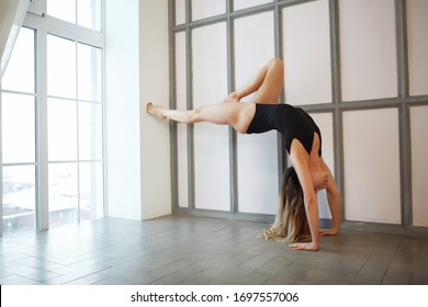 Young skinny woman in black sportwear doing yoga handstand near the window in her home during quarantine. What to do at home during self-isolation. Stay home