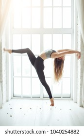 Young skinny woman doing yoga handstand against window