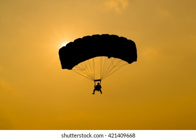 Young skydiver parachute in the air on sunset.