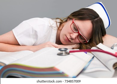 Young sleeping female nurse student  wearing white scrubs, laying on school books with stethoscope