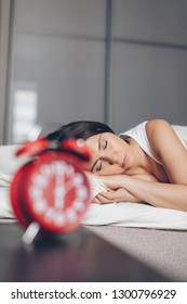 Young sleeping woman in bedroom at home and Alarm clock closeup