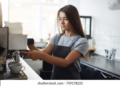 Young and sleepy female barista concentrated on using a coffee machine to brew some fresh ground beans to wake up.
