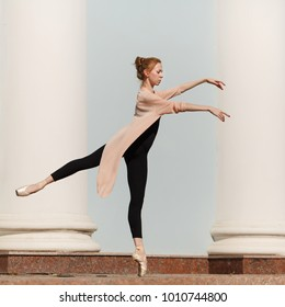 A young slender ballerina dances in the street. She stands on tiptoe. City Performance