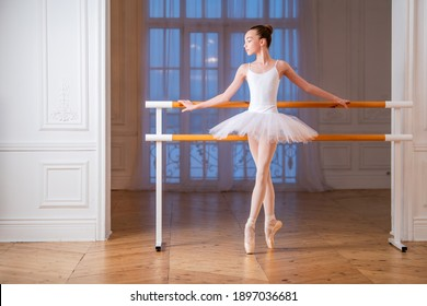 young slender ballerina in a white tutu standing on pointe at a ballet bar in a beautiful white hall in front of a mirror.