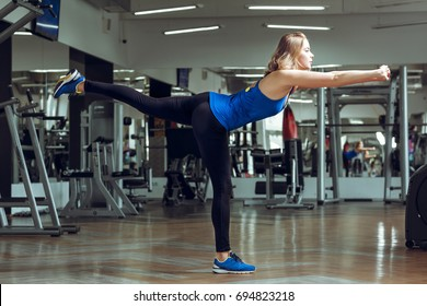 Young slender blond woman doing exercises in a gym