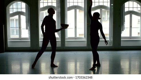 A young slender blonde girl is in a large Studio with large Windows, she is holding a bowl and a stick, creating a massage with sound vibrations, and in the background is another girl who is dancing.