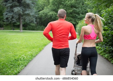 A young slender blonde mother runs during training next to an unidentified husband athlete and talks to him and carries a pram with a child in the city park