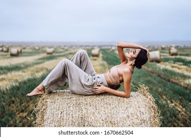 Young slender brunette girl with bright makeup in beige top with bare stomach and gray pants, lying on hay, posing for camera, photo shoot on field, blue sky
