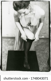 A young slender girl in clothes with a deep neckline puts on a stocking on her leg. Image contains grit, soft focus, and other artifacts of analog photography. Film photography.
