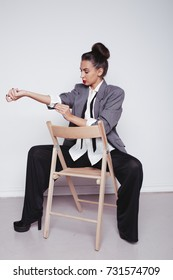 young slender girl dressed in a male business suit. emotional portrait. clean skin and hair in a bun. big things on the fragile woman. the concept of feminism in society. office worker