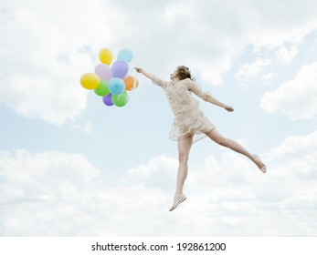 Young slender girl flying in the sky lace dress with bright balloons in her hands