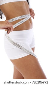 A young slender girl measures a waist with a centimeter over white background. Sport, fitness, diet, weight loss and healthcare concept