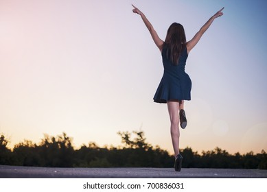 A young slender girl with sexy legs in heels in a miniskirt stands on a sunset background with her hands raised on one leg depicting joyful and vivid emotions.
