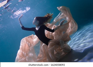 Young Slender Girl Underwater with a Cloth. Water Magic. Underwater Photography. Art
