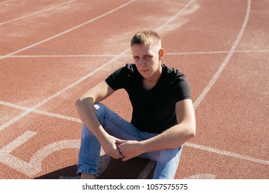 young slender guy with a short haircut and problematic skin walks around the city on a summer day. street style in clothes: leaky jeans and black t-shirt. posing on the site of the stadium