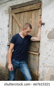 young, slender guy walking in the city. big ears and short hair. the man is dressed in jeans and a dark shirt. urban environment and street style. a walk on a summer day. Wallpaper for desktop