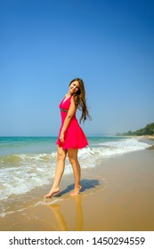Young slender long-haired brunette in red dress standing barefoot on tropical beach with yellow sand against the sea and blue sky on a hot day. Vertical photo of beautiful girl walking along the surf.