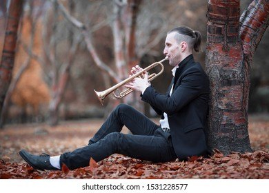 young slender man in black suit plays golden jazz trumpet sitting near brown tree with many fallen brown leaves below in gloomy autumn park