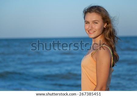 Young Slender Teen Girl With Flowing Long Hair On The Beach In The Summer Sun