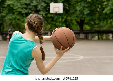 Young slender teenage girl playing basketball throwing the ball, view from behind
