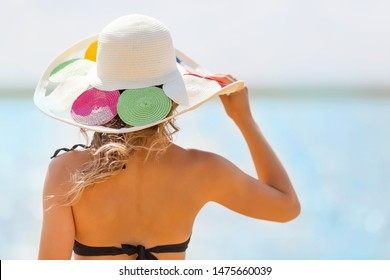 Young slender woman holds hat on her head with a strong sea wind