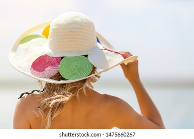 Young slender woman holds a hat on her head with a strong sea wind.