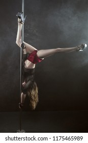 Young and slender woman shows a dance on a pole.