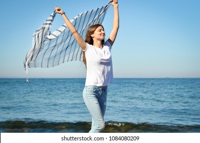 young slender woman is standing with a striped scarf in her hands on the beach and the wind is blowing on her