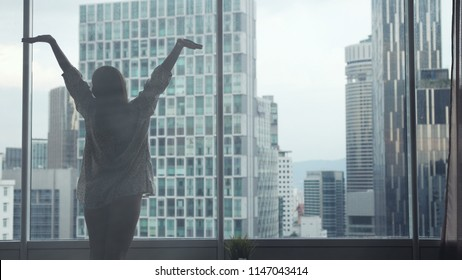 Young slender woman stands by the big window, stretches hands up, wake up in the morning