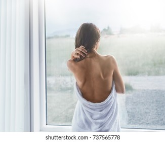 young slender woman stands at a window wrapped in a towel. woman after the shower, she has a back open, she looks out the window. Beautiful young woman after shower standing near window at home