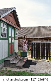 a young slender woman in a vintage dress descends the steps from a village shabby house to a country yard with sheds holding an old-fashioned green suitcase