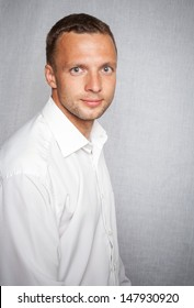 Young slightly smiling man in white shirt over gray background. Studio portrait