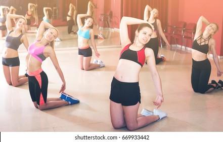 Young slim athletic females exercising modern dances in studio