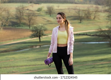 A young slim athletic girl in sportswear performs a set of exercises. Fitness and healthy lifestyle  against the background of green spring pasture hills.